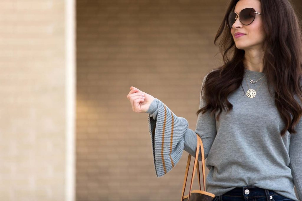 Alissa Weikel of Lipgloss & Labels wearing a grey bell sleeve sweater and dark jeans