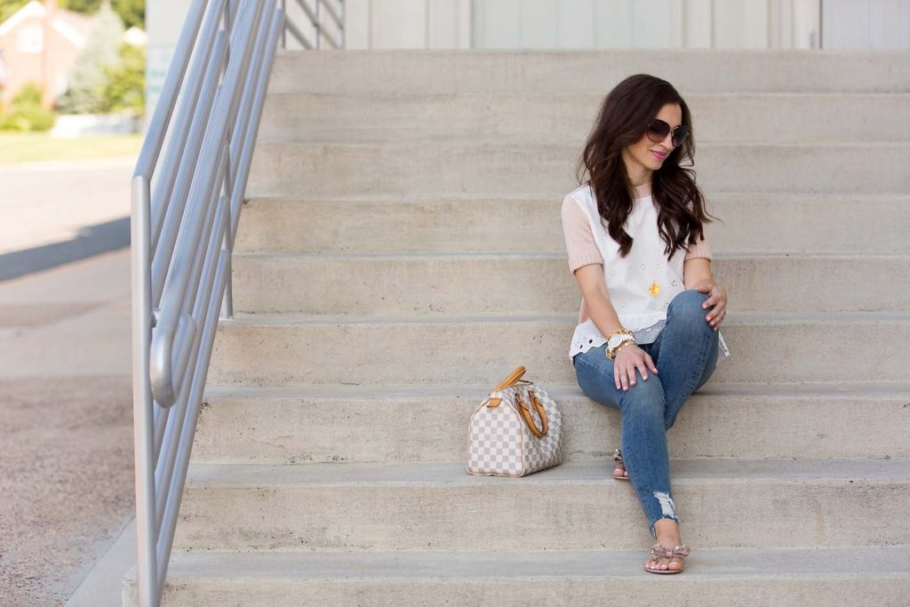 Alissa Weikel of Lipgloss & Labels wearing an eyelet peplum sweater and skinny jeans