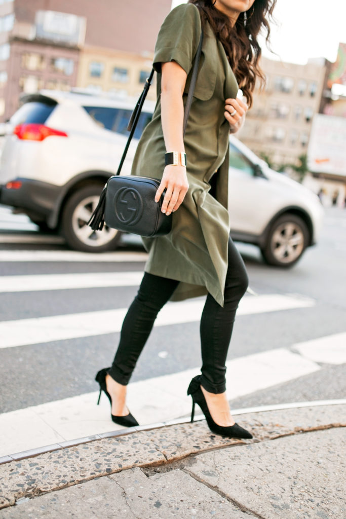 olive trench vest and black jeans