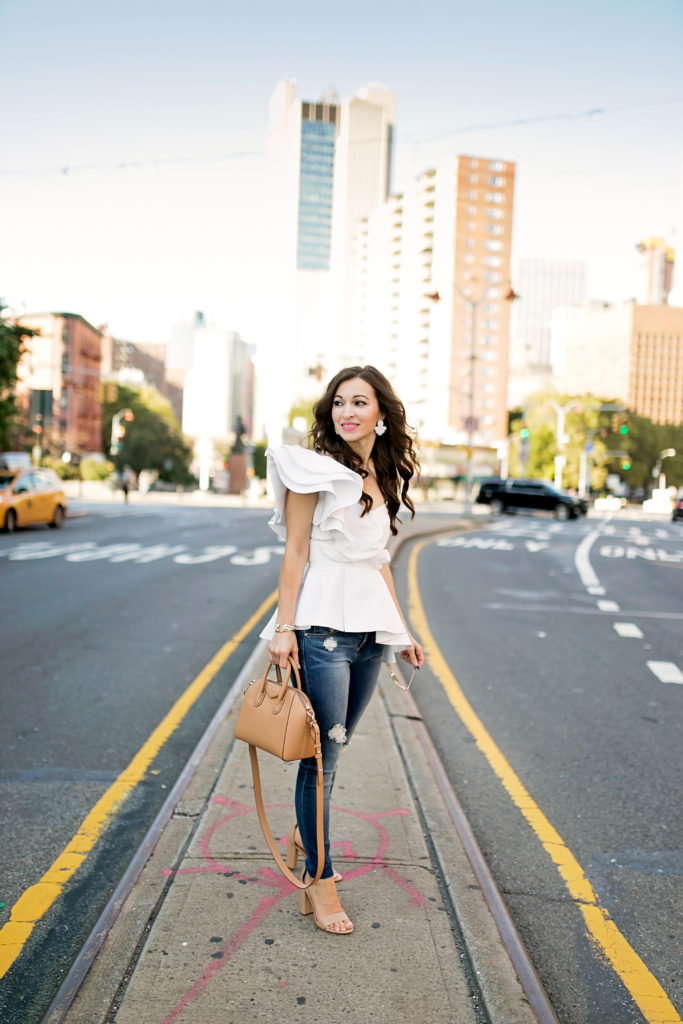 Alissa Weikel of Lipgloss & Labels wearing a white ruffle statement top