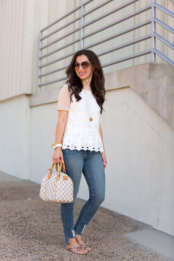 Alissa Weikel of Lipgloss & Labels wearing an eyelet peplum sweater and high waisted jeans