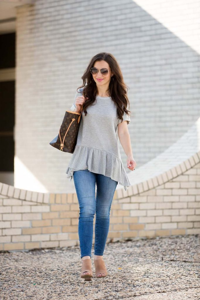 Alissa Weikel of Lipgloss & Labels wearing a grey peplum sweatshirt