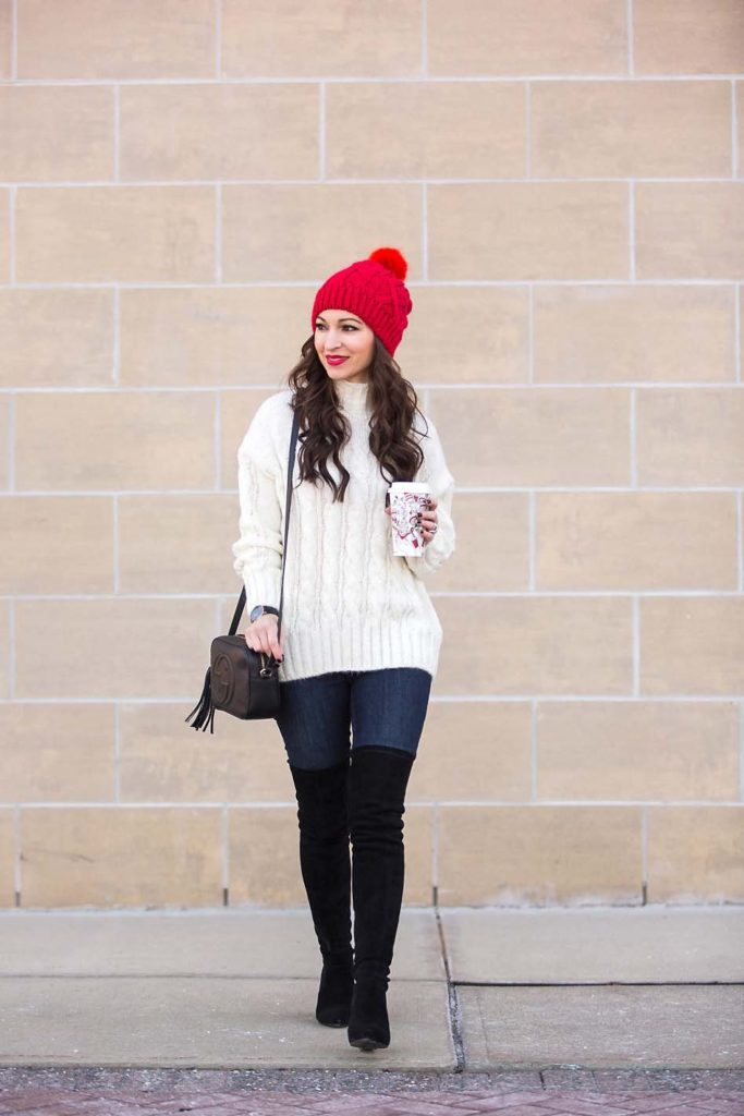 festive winter outfit red beanie ivory sweater black over the knee boots