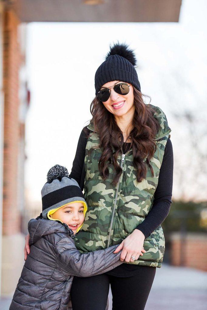 mother son winter style camo puffer vest grey puffer coat black pom beanie
