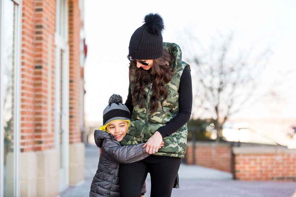 mother son winter style grey puffer coat striped hat black beanie camo vest